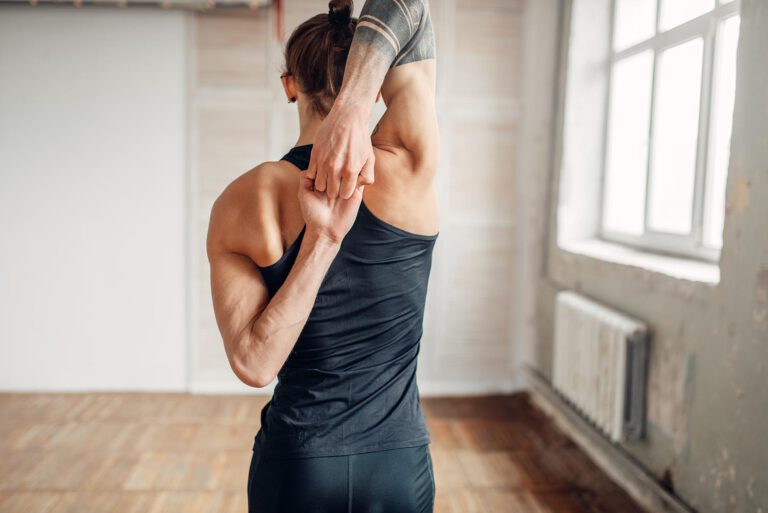 Male yoga on training, flexibility of human body. Balance exercise on mat in gym with grunge interior. Fit workout indoors